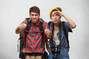 Bearded guy in plaid shirt with backpack driving car, holding tight driving wheel while his girlfriend next to him keeping hand on her forehead, staring into distance with shocked amazed look