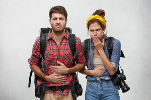 Food poisoning, nausea and sickness concept. Portrait of young man and woman tourists feeling stomach ache, suffering from diarrhea after they ate some exotic food during journey in Asian country