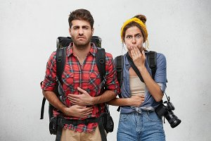 Studio shot of bearded young man having painful expression holding hands on his stomach, feeling sick because of diarrhea, his girlfriend covering mouth,about to throw up. Tourism and adventure