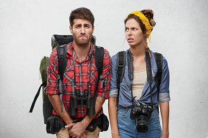 Caucasian male taveler looking upset while wanting to go in toilet, holding big backpack and having binoculars on his neck and his young female companion who is looking at him with annoyance