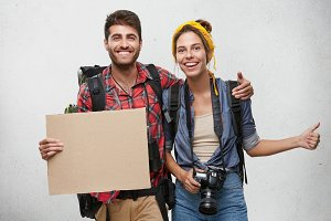 Young tourists posing against white background: smiling man holding blank cardboard and big rucksack embracing his wife who is holding camera and backpack showing ok sign. Tourism, travelling concept