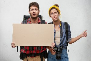 Picture of tired worn out young couple of Caucasian tourists holding blank cardboard with copy space for your content, hitchhiking in Europe, trying to catch a car in countryside. Travel and hitchhike
