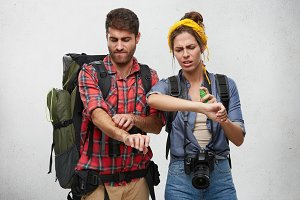 Studio shot of fashionable young female with photo camera looking frustrated using spray against Mosquitos, her bearded husband with rucksack scratching arms. Hiking, trekking, journey and vacations