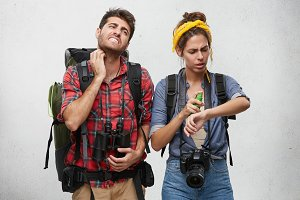 Mosquitos attack. Displeased angry young European couple carrying backpacks itching, scratching spots from insects bites, having painful frustrated looks. People, traveling, tourism and adventure