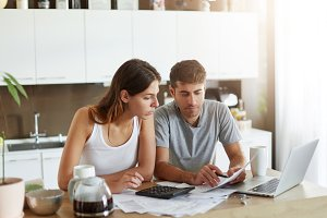 Portrait of serious man and female sitting at kitchen table, dealing with financial issues, holding documents. Family couple calculating their debts while sitting together at kitchen. Business concept