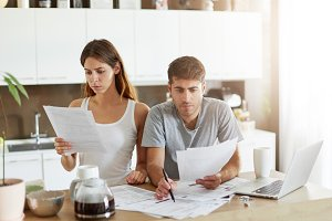 Serious male and female sitting close to each other, looking through finances, planning family budget while sitting at kitchen table, using modern laptop computer. Family and finances concept