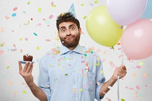 Young bearded man wearing party hat and formal shirt, looking with great hesitation into camera, shrugging his shoulders, keeping cupcake and balloons in hands, isolated over white background