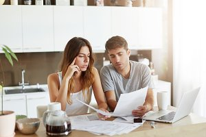Handsome young man showing his calculations to wife, consulting something with her. Young couple studying documents while sitting together at kitchen table. Family business and finances concept