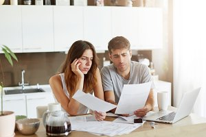 Family entrepreneurs calculating their budget and bills, looking seriously in documents while sitting in kitchen and drinking coffee, using modern laptop. Concentrated couple working with papers