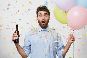 Portrait of good looking man with thick beard and dark eyes looking surprisely into camera, realizing that party is over and he is late. Shocked man in party hat, holding bottle and colorful balloons