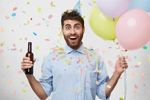 Happy excited man with beard, wearing party hat and formal clothes, holding bottle with drink and colorful balloons isolated over white background. Cheerful man coming to congratulate his friend