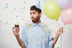 Portrait of handsome guy celebrating something, holding cupcake in hand looking at it with surprisment, whistling in party horn and keeping balloons. Bearded man coming to party. Festive concept