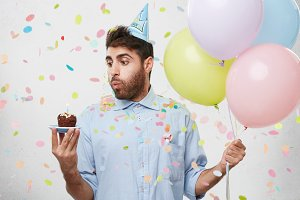 Young man having birthday, receiving congratulations from friends, holding colorful balloons, blowing at candle of cupcake, making wish. Bearded attractive young man coming to birthaday party