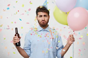Sad attractive man with beard keeping bottle with alcohol drink in one hand and colorful balloons in other, having bad mood as party finishes, wanting to continue celebration. People, party, event