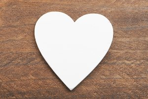 Top view of a white heart on wooden background. Isolated.