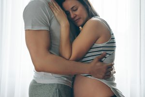 Pregnant woman embraced by her husband