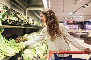 Woman buying lettuce in supermarket.