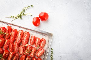 Dried tomatoes in baking tray and spatula on blue wooden background