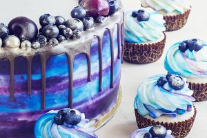 Bright festive blue cake with berries and chocolate and cupcakes with cream