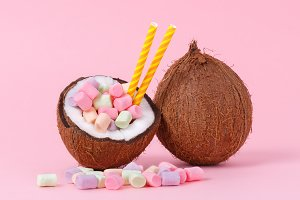 Marshmallow in half coconut on a pink background. Minimal concept