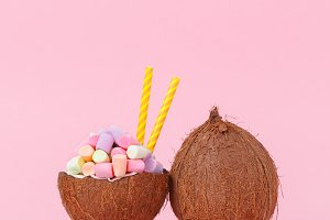 Coconut milk with marshmallow in half coconut on a bright background. Minimal style