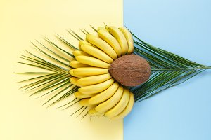 Coconut and bananas on palm leaves on a bright color background.