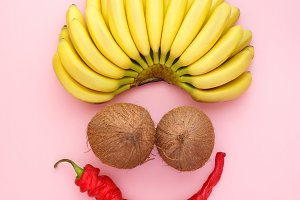 Bananas, coconuts on a bright background. Funny face composed of bananas, coconuts and peppers. Clown Face from fruits