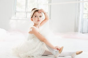 The little balerina in white tutu in class at the ballet school