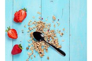 dry muesl with black teaspoon and fresh strawberries