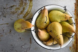 Pears as small comic characters in bowl. Rustic vintage style