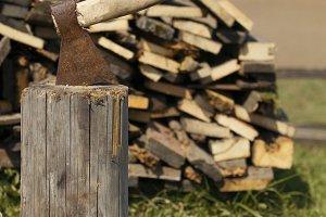 Old axe stuck in stump near woodpile - farm in Russia