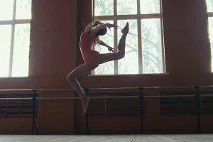 Ballerina performs acrobatics tricks in studio