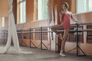 Young woman dancer use smartphone in a ballet room