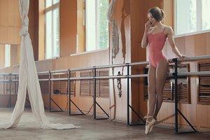 Girl ballerina use smatphone in a dancing room