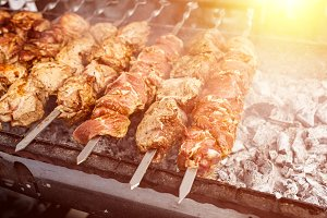Grilled kebab cooking on metal skewer. Roasted meat cooked at barbecue. BBQ fresh beef meat chop slices. Traditional eastern dish, shish kebab.