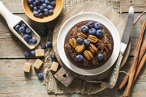 Top view of chocolate crazy pie with chocolate chip topping, juicy blueberries, pecans on a simple wooden background with a vintage silver knife for a cozy autumn tea