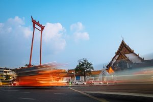 The Giant Swing with Temple of Buddha at dusk. Bangkok night city downtown, Thailand. Modern city skyline at twilight with lights trails from fast moving cars blur, Asia