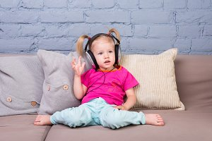 Baby girl sitting on sofa with pillows and listening to music in big headphones put on head.