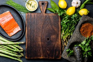 Ingredients for cooking. Raw salmon fillet, asparagus and herbs around wooden board. Food cooking background with copy space. Top view.