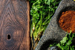 Herbs and spices around wooden cutting board. Top view with copy space