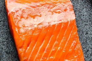 Raw salmon filet on black iron plate. Top view