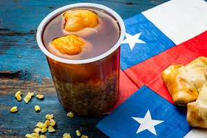 Chilean independence day concept. fiestas patrias. Chilean typical dish and drink on independence day party, 18 september. Mini empanadas, mote con huesillo, wine with toasted flor, chicha and tipical play emboque