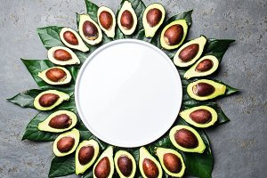 Avocado. Frame made from avocado palta and avocado tree leaves around white plate. Guacamole ingredients. Healthy fat, omega 3 concept Half of avocado. Top view. Copy space.