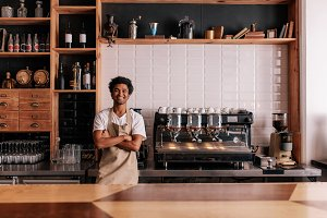 Barista in apron looking at camera