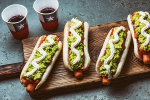 Chilean Completo Italiano. Hot dog sandwiches with tomato, avocado and mayonnaise served on wooden board with drink in paper cup . Top view. Independence Day concept