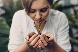 Woman smelling small plant