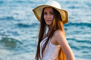 Young fit woman in summer outfit and wearing hat by seaside