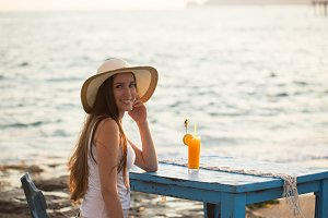 Beautiful young woman seating in cafe by seaside with orange jui