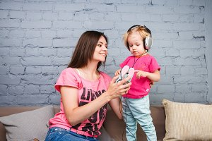 Mom and daughter listen to music in big headphones put on their head, sitting on the sofa. Holds the phone.