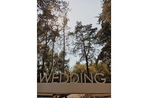 wedding inscription with big white letters on a background of green park.